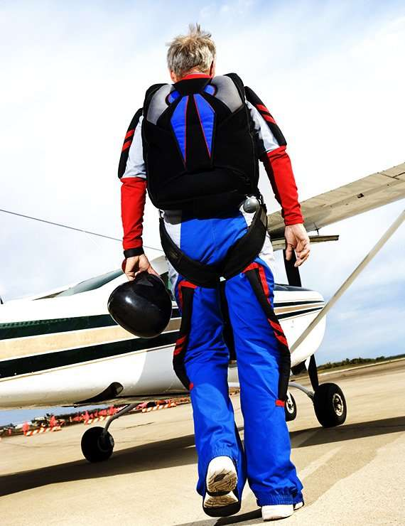 Older man approaching a plane to go skydiving