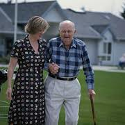 An elderly man walking assisted with a cane