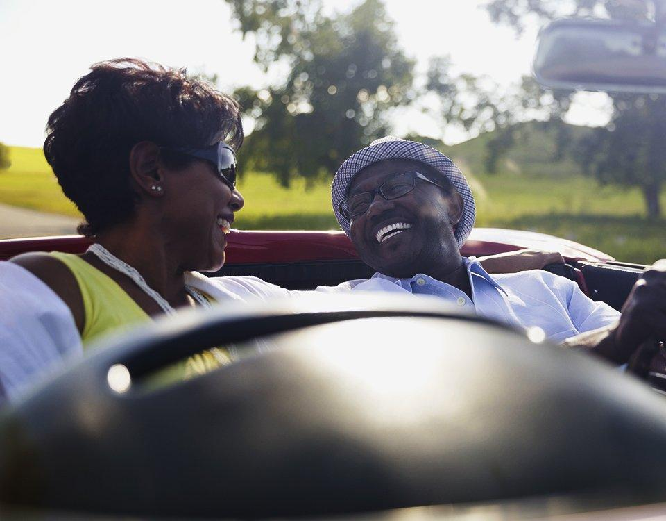 A couple laughing in a convertable