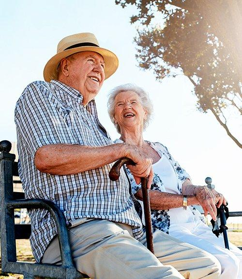 An older couple together outside laughing with each other
