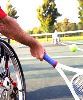 A man playing tennis in a wheelchair