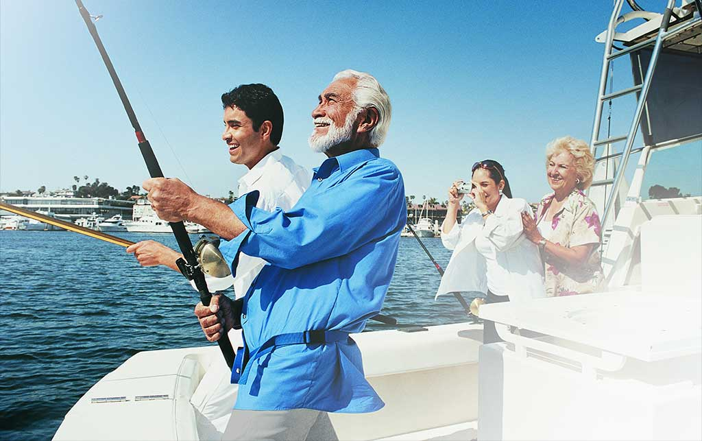 Mature man fishing on the boat with his family